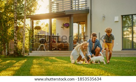 Smiling Father, Mother and Son Pet and Play with Smooth Fox Terrier Retriever Dog. Sun Shines on Idyllic Happy Family with Loyal Pedigree Dog have Fun at the Idyllic Suburban House Backyard Royalty-Free Stock Photo #1853535634