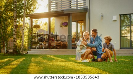Smiling Father, Mother and Son Pet and Play with Smooth Fox Terrier Retriever Dog. Sun Shines on Idyllic Happy Family with Loyal Pedigree Dog have Fun at the Idyllic Suburban House Backyard Royalty-Free Stock Photo #1853535643