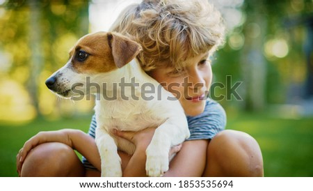 Cute Boy Holds His Favourite Pedigree Dog Friend while Having Picnic Outdoors on the Lawn. He Pets and Cuddles His Little Smooth Fox Terrier. Idyllic Summer House. Royalty-Free Stock Photo #1853535694