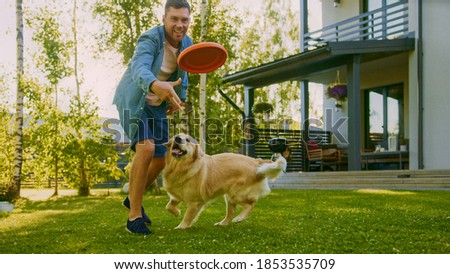 Handsome Man Plays Catch flying disc with Happy Golden Retriever Dog on the Backyard Lawn. Man Has Fun with Loyal Pedigree Dog Outdoors in Summer House Backyard. Royalty-Free Stock Photo #1853535709