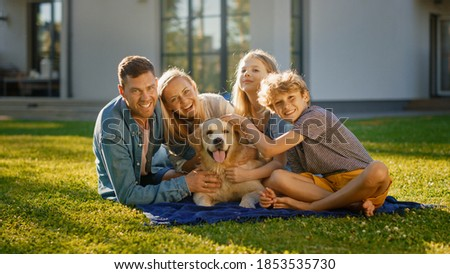 Portrait of Father, Mother and Son Having Picnic on the Lawn, Posing with Happy Golden Retriever Dog. Idyllic Family Have Fun with Loyal Pedigree Dog Outdoors in Summer House Backyard.