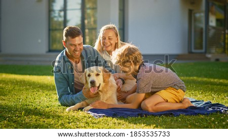 Portrait of Father, Mother, and Son Having Picnic on the Lawn, Posing with Happy Golden Retriever Dog. Idyllic Family Have Fun with Loyal Pedigree Doggy Outdoors in Summer House Backyard.