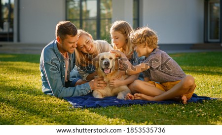 Smiling Portrait of Beautiful Family of Four Having Picnic on the Lawn, Posing with Happy Golden Retriever Dog. Idyllic Family Have Fun with Loyal Pedigree Dog Outdoors in Summer House Backyard.