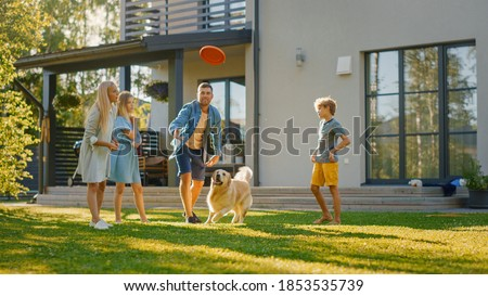 Smiling Beautiful Family of Four Play Fetch flying disc with Happy Golden Retriever Dog on the Backyard Lawn. Idyllic Family Has Fun with Loyal Pedigree Dog Outdoors in Summer House Backyard Royalty-Free Stock Photo #1853535739