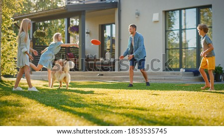 Smiling Beautiful Family of Four Play Fetch flying disc with Happy Golden Retriever Dog on the Backyard Lawn. Idyllic Family Has Fun with Loyal Pedigree Dog Outdoors in Summer House Backyard Royalty-Free Stock Photo #1853535745