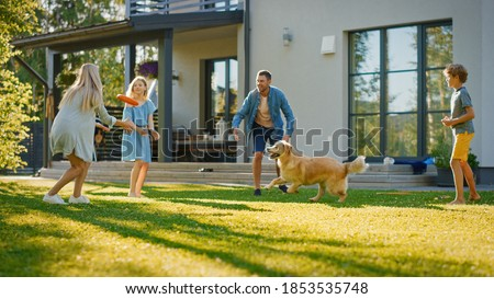 Smiling Beautiful Family of Four Play Fetch flying disc with Happy Golden Retriever Dog on the Backyard Lawn. Idyllic Family Has Fun with Loyal Pedigree Dog Outdoors in Summer House Backyard Royalty-Free Stock Photo #1853535748