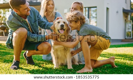 Smiling Beautiful Family of Four Posing with Happy Golden Retriever Dog on the Backyard Lawn. Idyllic Family Cuddling Loyal Pedigree Dog Outdoors in Summer House Backyard. Royalty-Free Stock Photo #1853535775