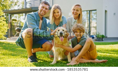 Smiling Beautiful Family of Four Posing with Happy Golden Retriever Dog on the Backyard Lawn. Idyllic Family Have Fun with Loyal Pedigree Dog Outdoors in Summer House Backyard.
