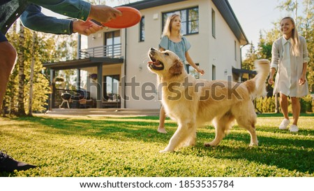 Smiling Beautiful Family of Four Play Catch flying disc with Happy Golden Retriever Dog on the Backyard Lawn. Idyllic Family Has Fun with Loyal Pedigree Dog Outdoors in Summer House. Royalty-Free Stock Photo #1853535784