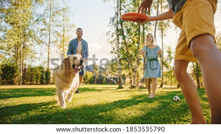Smiling Beautiful Family of Four Play Soccer with Happy Golden Retriever Dog at the Backyard Lawn. Idyllic Family Having Fun with Loyal Pedigree Puppy Outdoors in Summer House. Handheld Ground Shot Royalty-Free Stock Photo #1853535790