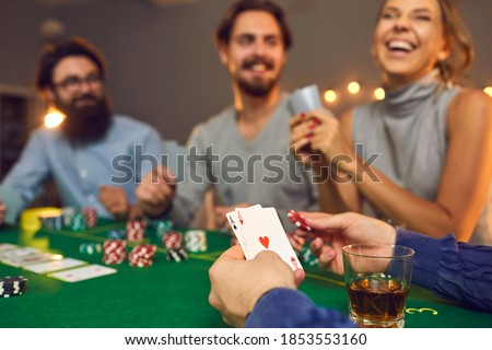 Mans hands holding playing cards with aces, poker chips and drink in glass during poker gambling over smiling friends faces at background, close-up, selective focus. Gambling, casino, poker concept Royalty-Free Stock Photo #1853553160