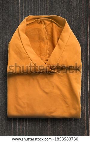 Folded yellow shirt on dark wooden background #1853583730