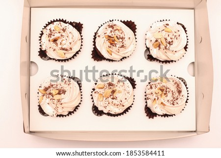 Six chocolate brownies with white cream in an open craft box from above on a white plate. Top view picture