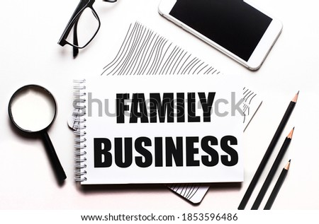 On a white background glasses, a magnifier, pencils, a smartphone and a notebook with the text FAMILY BUSINESS