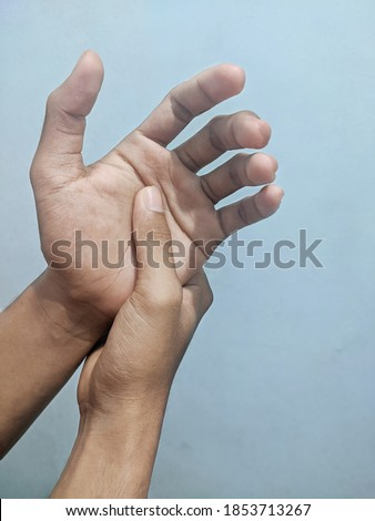 Numb or tingling man's hand on a blue background
