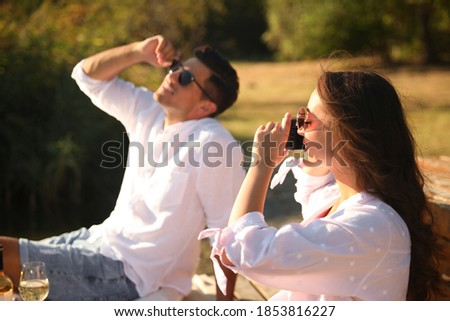 Woman taking picture of boyfriend outdoors at picnic