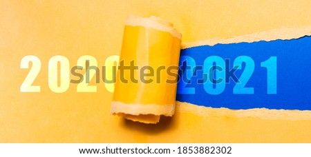 Happy new year, new start, new page of life; resolution concept. Text of 2021 on blue background in hole of torn yellow textured paper with text of 2020. Royalty-Free Stock Photo #1853882302