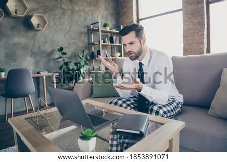Photo of smart marketer man sit divan white shirt black tie necktie sleep night wear work remote laptop discuss partners employees start up strategy online meeting briefing in house indoors