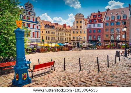 Traditional blue water pump with gryphon head crest from Szczecin city emblem and old town square in background. Gryphon is Stettin emblem since 1360 Royalty-Free Stock Photo #1853904535