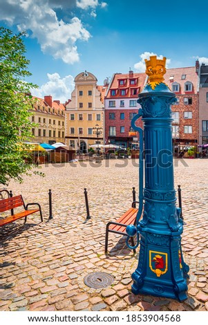 Traditional blue water pump with gryphon head crest from Szczecin city emblem and old town square in background. Gryphon is Stettin emblem since 1360 Royalty-Free Stock Photo #1853904568