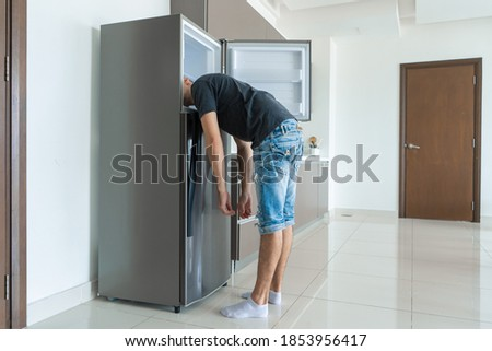 On a hot day, the guy cool down with his head in the refrigerator. Broken air conditioner. Royalty-Free Stock Photo #1853956417
