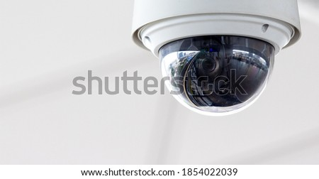 Closeup of white dome type cctv digital security camera installed on ceiling for observation. Royalty-Free Stock Photo #1854022039