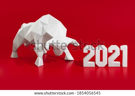 White volumetric paper bull papercraft and numbers 2021 on a red background, symbol of the year