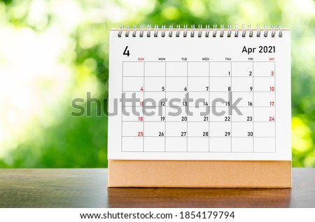 April 2021 Calendar desk for organizer to plan and reminder on wooden table on nature background.
