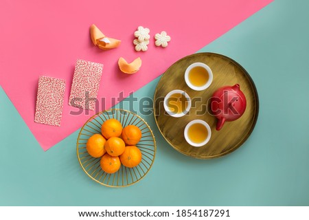 Group of Chinese New Year tea, red envelopes, tangerine and decorative items objects on light blue and pink background. Royalty-Free Stock Photo #1854187291