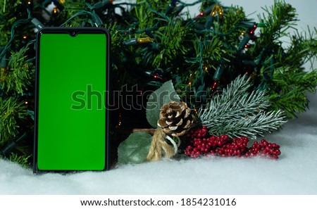 Smartphone with green screen on mobile phone near branch of Christmas tree on background of a Christmas tree with holiday lights, viewing a chroma key. Online shopping, sales