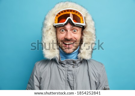Cheerful unshaven man with overjoyed expression smiles broadly wears ski goggles winter jacket with hood enjoys extreme winter sport poses against blue background. Snowboarding hobby concept Royalty-Free Stock Photo #1854252841