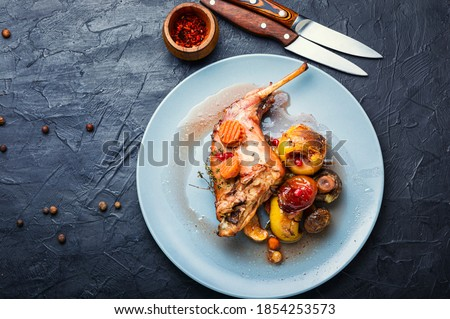 Baked rabbit leg with apples, carrots and mushrooms.