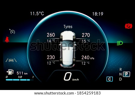TPMS (Tyre Pressure Monitoring System) with temperature measurement monitoring display on car dashboard panel. Checking tires pressures and temperature. Car cluster with speedometer and fuel gauge. Royalty-Free Stock Photo #1854259183