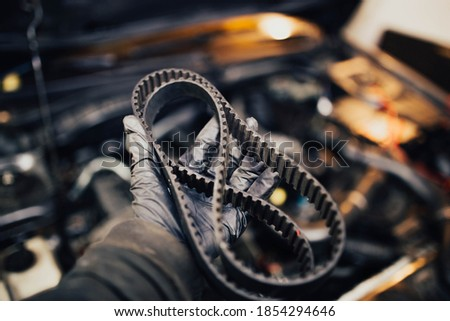 automotive timing belt in the hand of an auto mechanic. Royalty-Free Stock Photo #1854294646