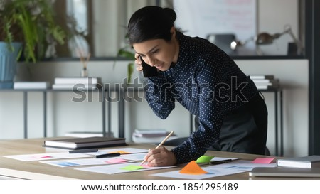 Serious Indian businesswoman talking on cellphone, writing notes on colorful sticky papers in office, employee checking financial documents, working with statistics, consulting client by phone call Royalty-Free Stock Photo #1854295489