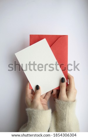 female hands in a sweater with manicure, holding a white sheet and a red envelope on a white background. postcard layout Royalty-Free Stock Photo #1854306304