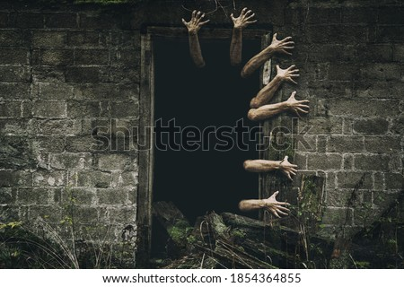Hands coming out from the door with dark background. Scary zombie hands.