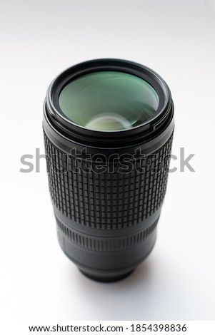 Photo of an isolated dslr telephoto lens seen from above. the clean and shiny front lens is visible. White background, for photo editing and advertising use. Optic, professional, pristine.