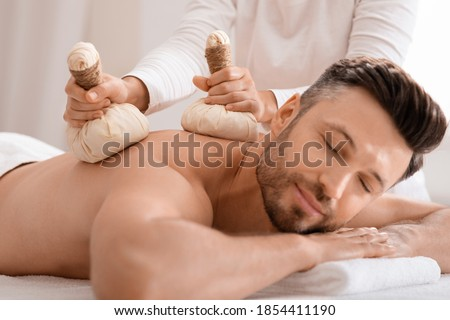 Herbal massage concept. Unrecognizable spa attendant making body massage for handsome man with herbal compress balls, luxury spa interior. Man enjoying herbal treatment at massage salon #1854411190