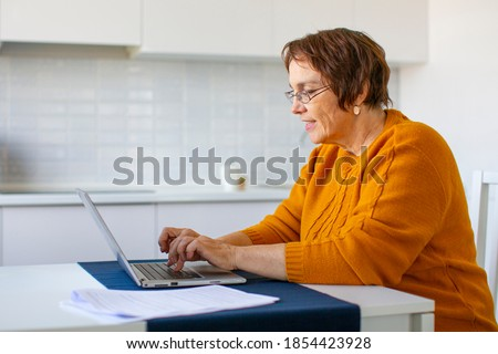 Photo of a smiley senior woman filling forms online in home interior. Online working. Royalty-Free Stock Photo #1854423928