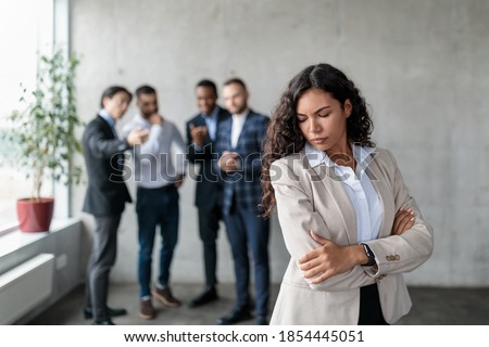 Workplace Sexism And Bullying. Unhappy Victimized Businesswoman Standing While Her Male Colleagues Whispering Behind Her Back Standing In Modern Office. Corporate Problems, Female Rights Concept Royalty-Free Stock Photo #1854445051