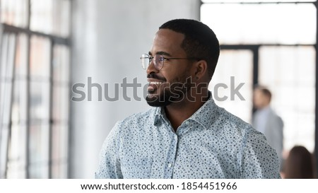 Pleasant thoughts. Happy successful african american businessman leader executive looking in office window with confident smile engaged in thinking of marketing strategy planning future perspectives