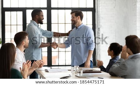 Perfect job! Friendly african american boss or team leader shaking hand of happy excited caucasian employee manager worker on staff meeting at boardroom demonstrating respect greeting with promotion Royalty-Free Stock Photo #1854475171