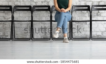 Waiting time. Cropped view of young female job applicant or public officer visitor sitting cross legged on chair in corridor close to hr or functionary office showing confidence patience, copy space Royalty-Free Stock Photo #1854475681