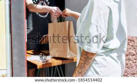 Cropped shot of woman taking paper bag with her order from hands of shop assistant while collecting her purchase from the pickup point. Selective focus. Web Banner Royalty-Free Stock Photo #1854514402