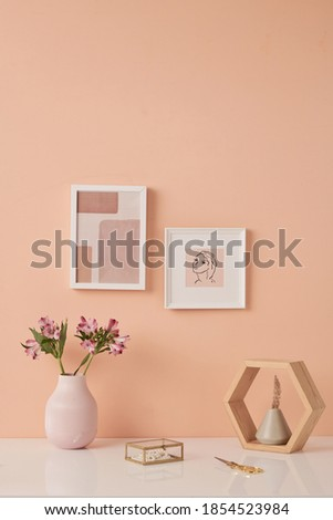 Two pictures in frames on pink wall by table with flowers in white ceramic vases, pearl necklace in glass box, scissors and small wooden shelf