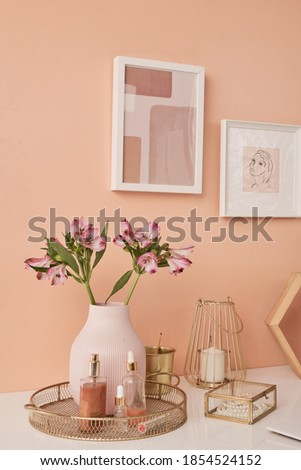 Two pictures in frames on pink wall by table with flowers in vase, beauty care products, candle, pearl necklace, golden bucket and other stuff