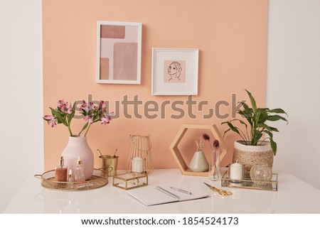 Workplace of interior designer by pink wall with two pictures in frames by table with flowers, beauty care products, candles and open copybook