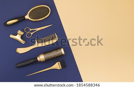 Hairdressing tools on a blue background and a yellow sheet with space for text. Gold hair salon accessories, comb, scissors, hair clip.  Royalty-Free Stock Photo #1854588346