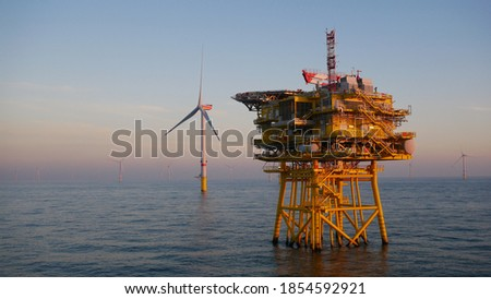 Offshore wind farm substation with turbine in North Sea Royalty-Free Stock Photo #1854592921